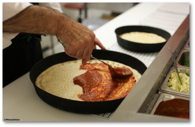 Pizzas being prepared at La Piazza pizza takeaway in Carlton